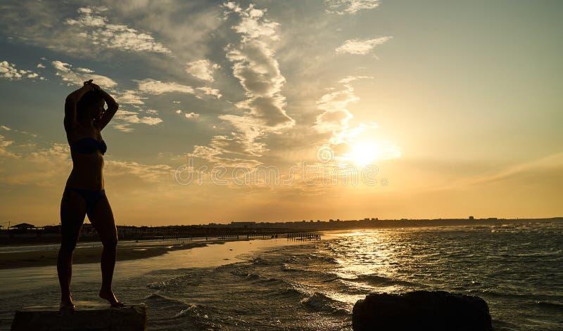 Kontur av den fria kvinnan på solnedgången på stranden royaltyfria bilder