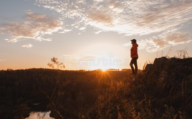 Kontur av den fria kvinnan som tycker om frihet som k?nner sig lycklig p? solnedg?ngen Fridfull avslappnande kvinna i ren lycka arkivbild