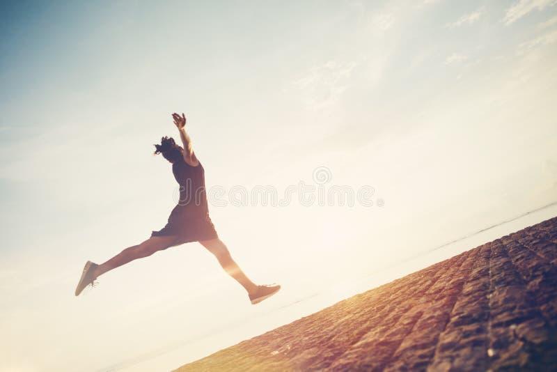 Kontur av den gladlynta kvinnan som hoppar nära havet Ha bra tid och gyckel arkivfoton