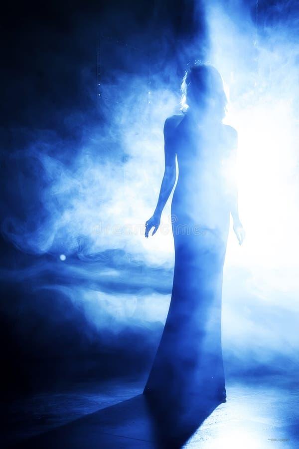 Kontur av den härliga flickan i blå scenisk dimma arkivfoto