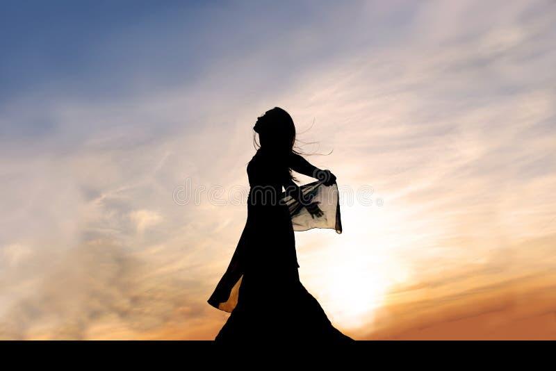 Kontur av den härliga unga kvinnan utanför på solnedgången som lovordar G royaltyfria foton