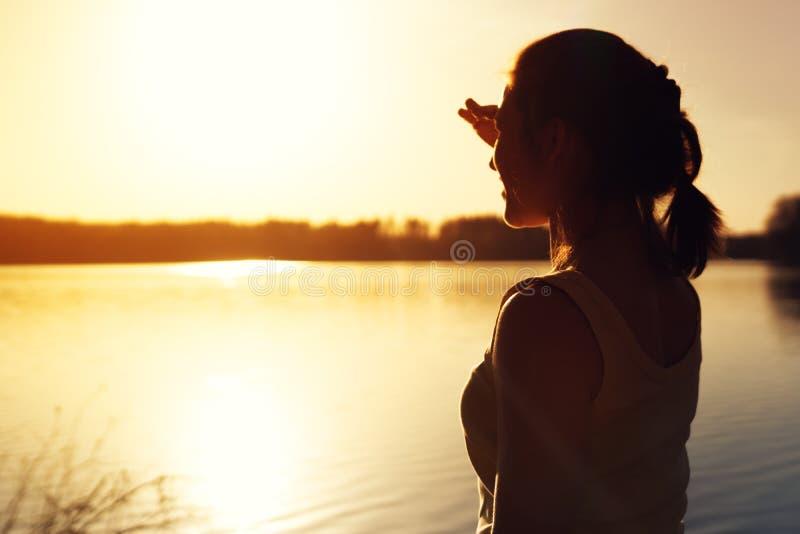 Kontur av den hållande ögonen på solnedgångnaturen för ung kvinna arkivfoton