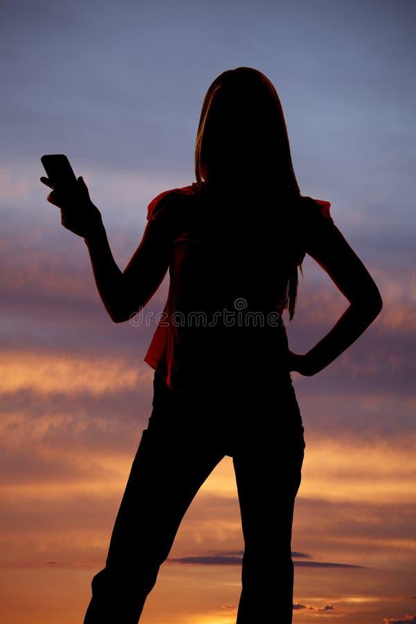Kontur av den hållande ut mobiltelefonsolnedgången för kvinna. royaltyfria foton