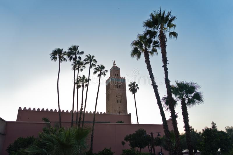 Kontur av den Koutoubia moskén och palmträd på solnedgången, Marrakech, Marocko arkivfoton