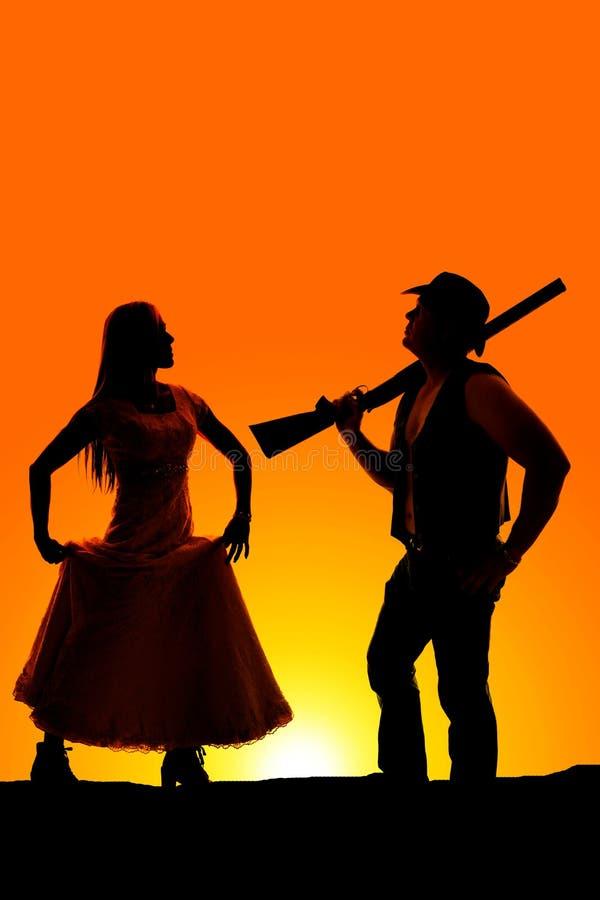 Kontur av den kvinnahållkjolen och cowboyen med vapnet i soluppgång royaltyfri fotografi