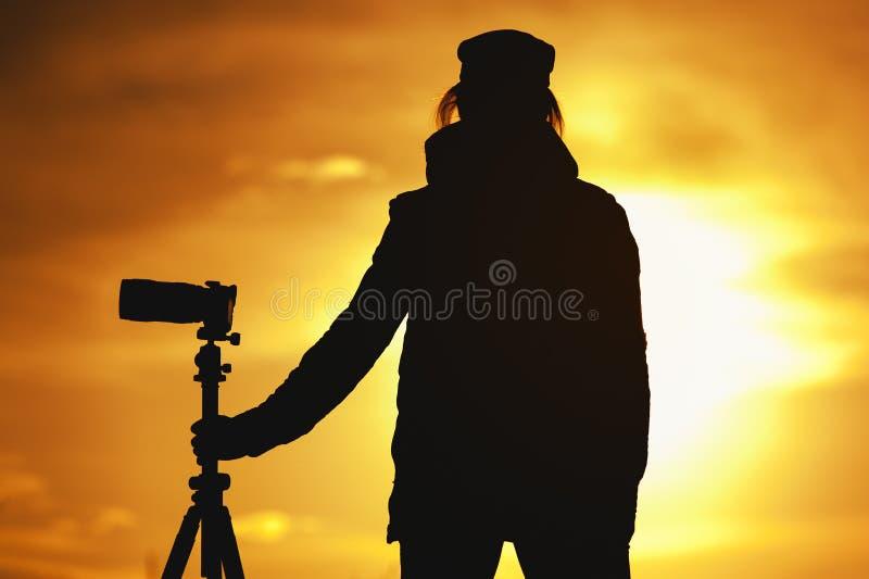 Kontur av den kvinnliga fotografen mot solnedgång fotografering för bildbyråer