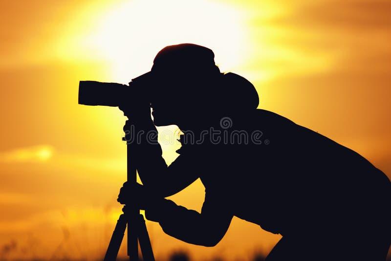 Kontur av den kvinnliga fotografen mot solnedgång royaltyfri foto