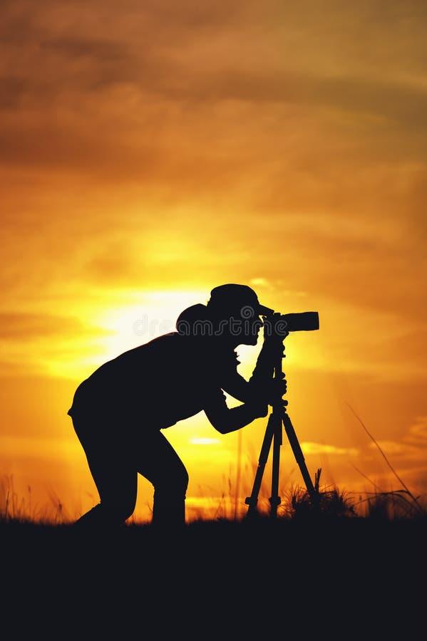 Kontur av den kvinnliga fotografen under solnedgång royaltyfri fotografi