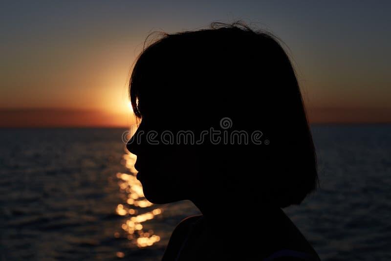 Kontur av den lilla charmiga flickan som står över havsnaturbakgrund och att tycka om härlig solnedgång eller soluppgång härlig n royaltyfri foto