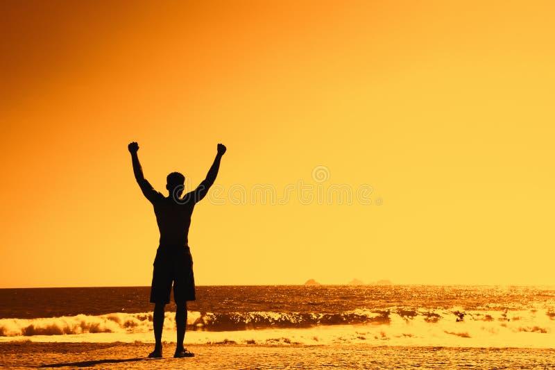 Kontur av den lyckade sportiga mannen på solnedgången med kopieringsutrymme arkivfoto