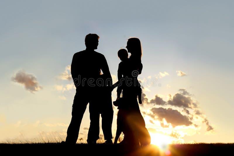 Kontur av den lyckliga familjen och hunden utanför på solnedgången royaltyfri fotografi
