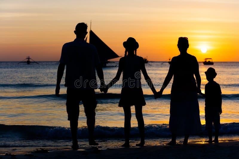 Kontur av den lyckliga familjen som har gyckel på stranden på solnedgångtiden royaltyfria foton