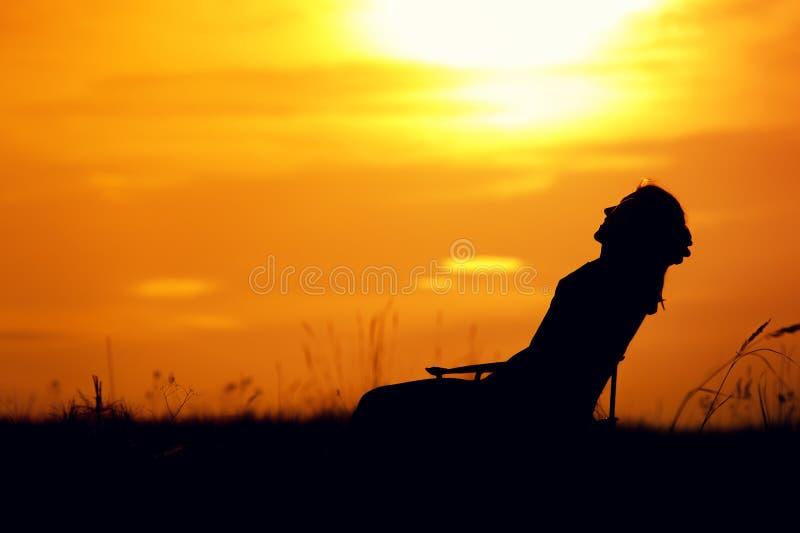 Kontur av den lyckliga kvinnan som tycker om solnedgångtid fotografering för bildbyråer