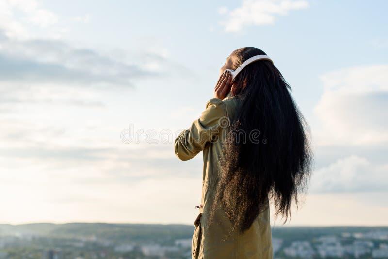 Kontur av den lyckliga le svarta afrikansk amerikankvinnan för barn med långt hår som lyssnar till musik Suddig cityscape på arkivfoton