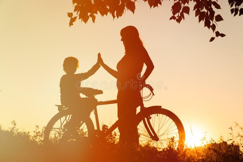 Kontur av den lyckliga modern och sonen som cyklar på solnedgången fotografering för bildbyråer