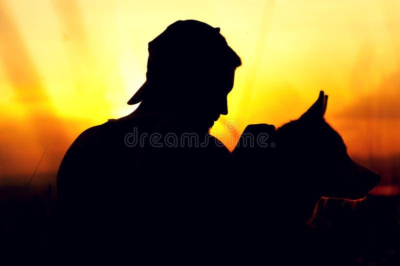 Kontur av den lyckliga unga mannen och hans skrovliga hund royaltyfri foto