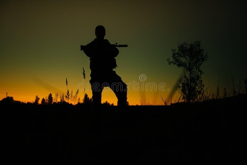 Kontur av den militära soldaten eller tjänstemannen med vapen på natten royaltyfri foto