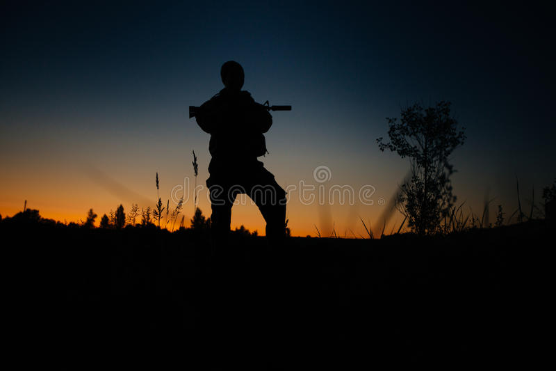 Kontur av den militära soldaten eller tjänstemannen med vapen på natten arkivbilder