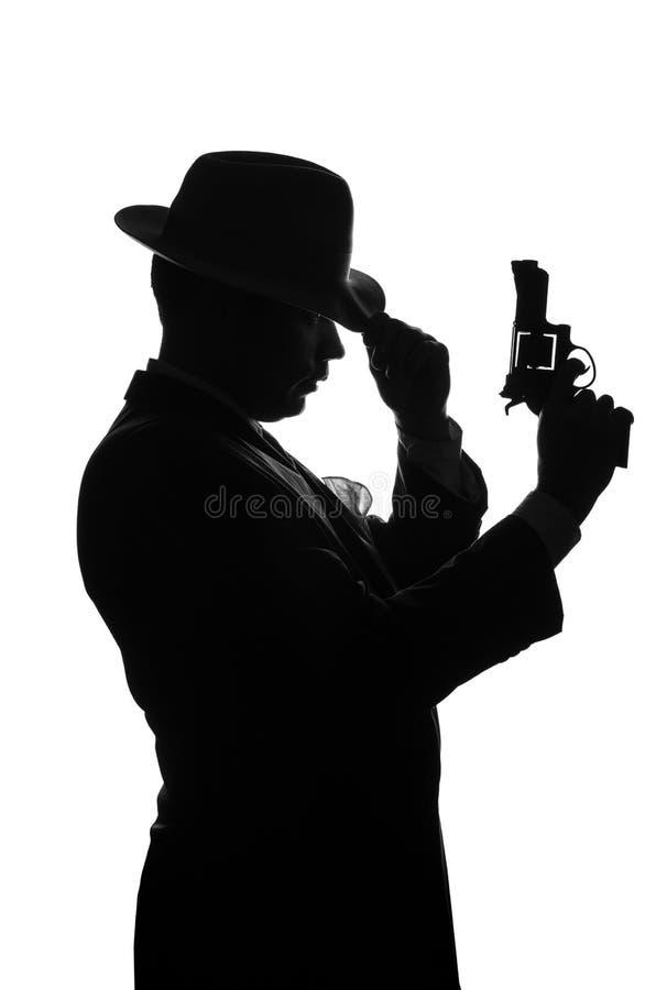 Kontur av den privata kriminalaren med ett vapen i assistent Medelstagsida till kameran och blickar som mafiosoen Al Capone Brott arkivfoto