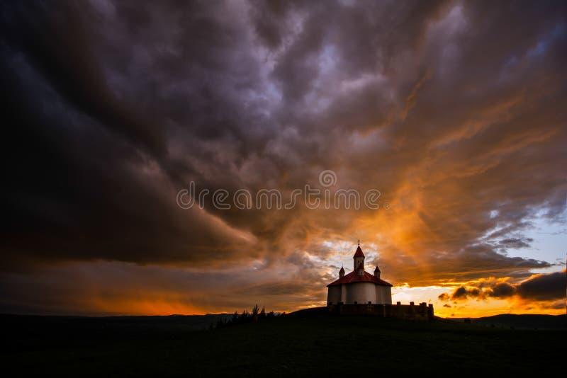 Kontur av den rumänska kyrkan med strålljus efter storm royaltyfri fotografi