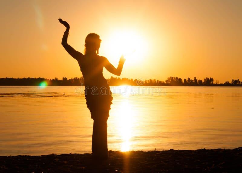 Kontur av den slanka kvinnan som dansar stam- dans på stranden arkivbilder