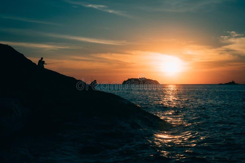 Kontur av den steniga klippan med fiskare under solnedgång på den tropiska ön i aftonen royaltyfri fotografi