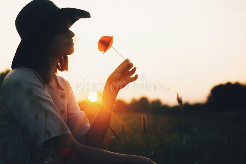 Kontur av den stilfulla flickan i blomma för vallmo för linneklänninginnehav i äng i solljus med blommor i lantlig sugrörkorg Boh fotografering för bildbyråer