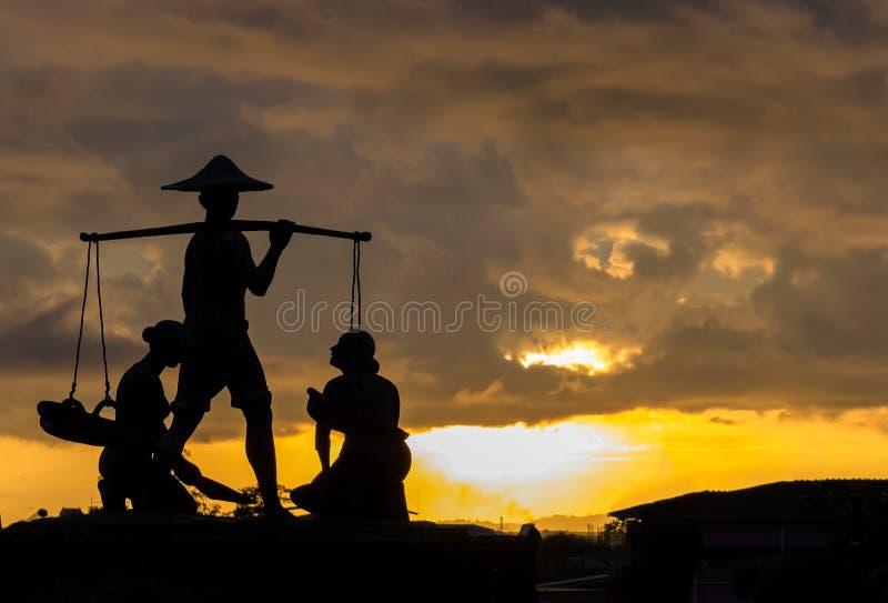 Kontur av den traditionella thailändska bonden Carry The Baskets av ris i hans hand med kvinnor på golvet på hörnet tillgänglig v arkivbilder