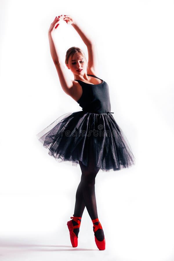 Kontur av den unga ballerina som poserar i vita ballerinakjol- och balettskor på vit bakgrund arkivbilder