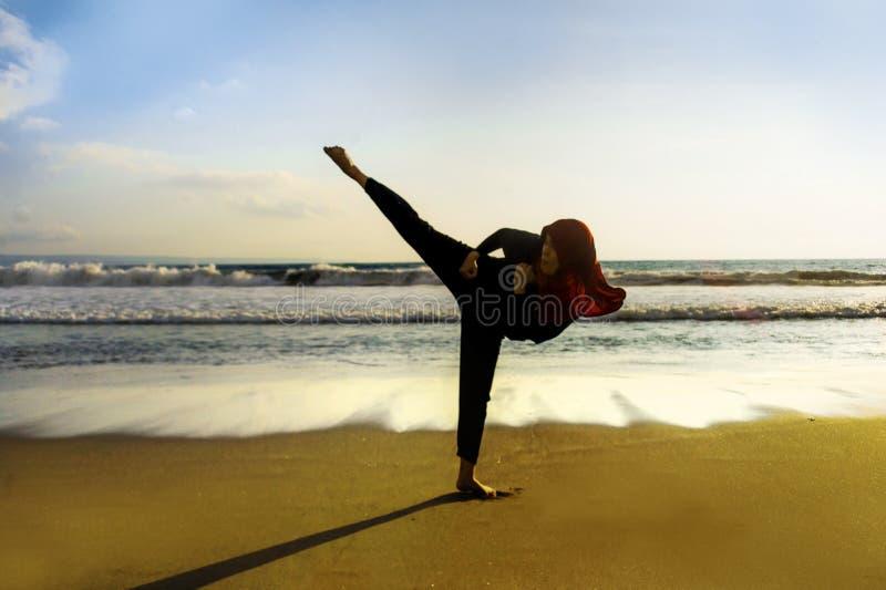 Kontur av den unga färdiga muslimska kvinnan som täckas i attack och kondition för spark för karate för kampsporter för halsduk f royaltyfria bilder