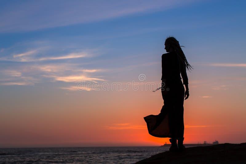 Kontur av den unga kvinnan i klänninganseende vid havet fotografering för bildbyråer