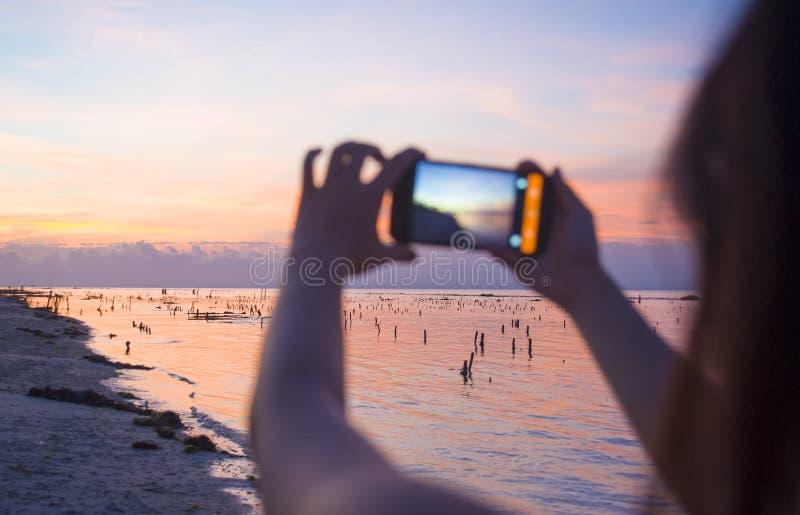 Kontur av den unga kvinnan med mobiltelefonkameran som tar bilden av den härliga Agung för för strandsolnedgånglandskap och monte fotografering för bildbyråer