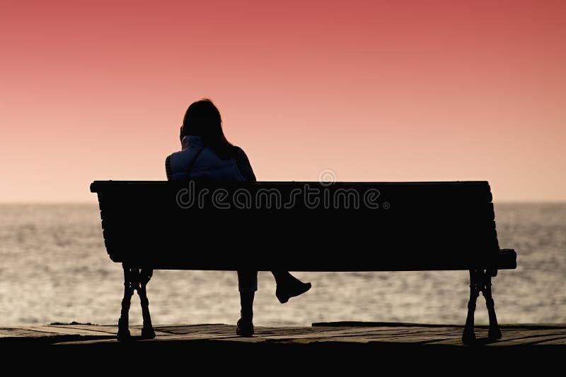 Kontur av den unga kvinnan som bara sitter på bänken fotografering för bildbyråer