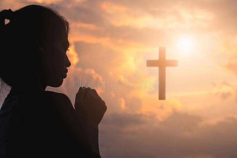 Kontur av den unga kvinnan som ber med ett kors på soluppgång, Christian Religion begreppsbakgrund royaltyfri bild