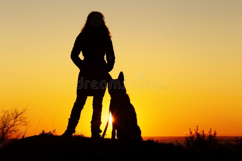 Kontur av den unga kvinnan som går med en hund i fältet på solnedgången, husdjur som sitter nära flickas ben på naturen, par av v royaltyfria foton