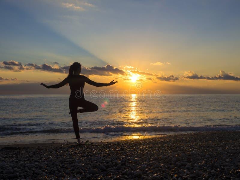 Kontur av den unga kvinnan som gör övningar på havsstranden under solnedgång Yoga, kondition och en sund livsstil arkivfoto