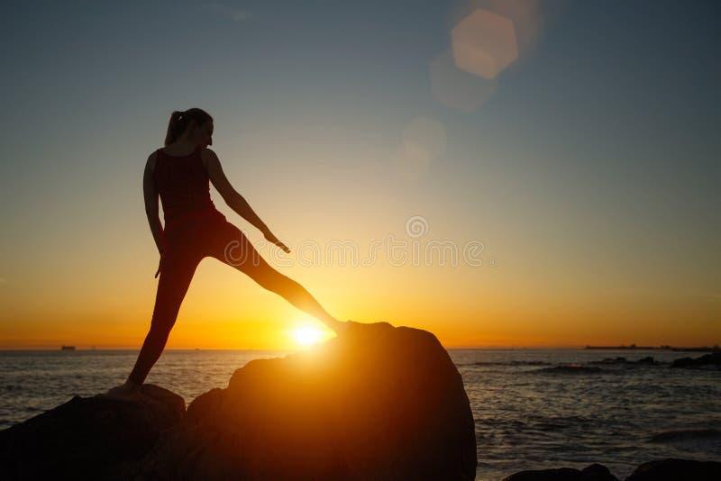 Kontur av den unga kvinnan som gör konditionövningar på stranden på att förbluffa solnedgång royaltyfri foto