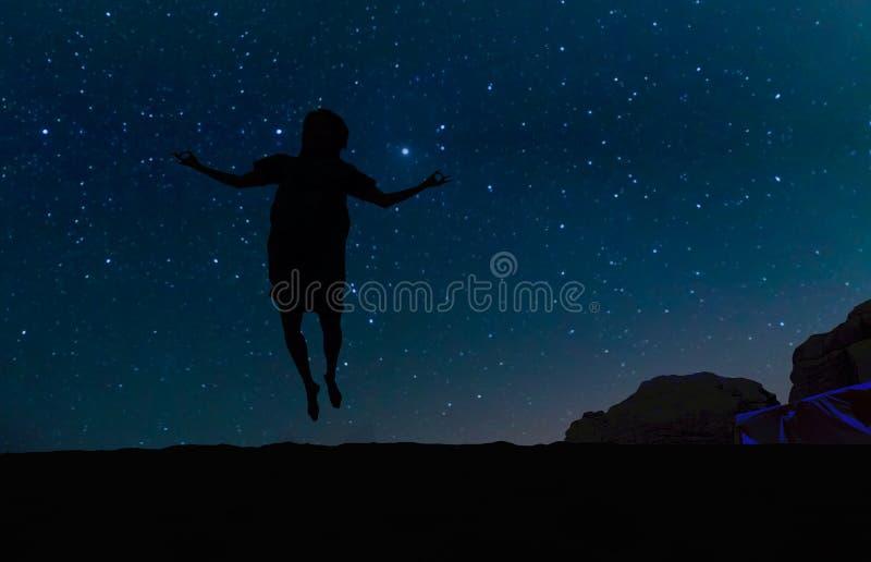 Kontur av den unga kvinnan som hoppar över sandkullen, under stjärnorna, Vintergatan och många stjärnor över berget på Wadi Rum d royaltyfria foton