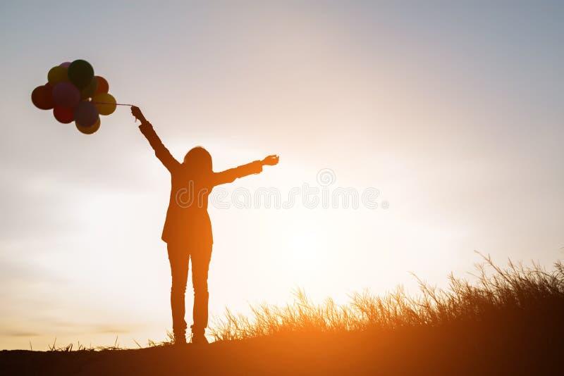 kontur av den unga kvinnan som rymmer färgrikt av ballonger med solen royaltyfri bild