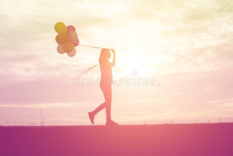 kontur av den unga kvinnan som rymmer f?rgrikt av ballonger med solnedg?ng arkivfoton