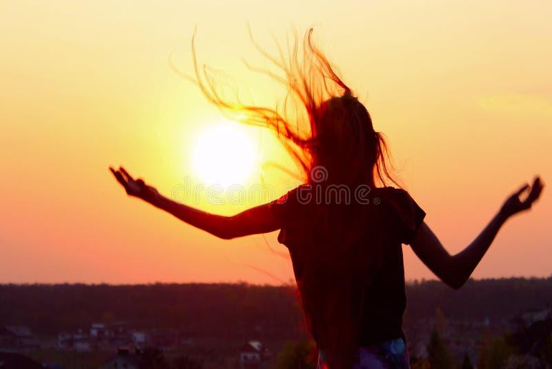 Kontur av den unga kvinnan som rymmer upp händer och ser till solnedgången royaltyfria bilder