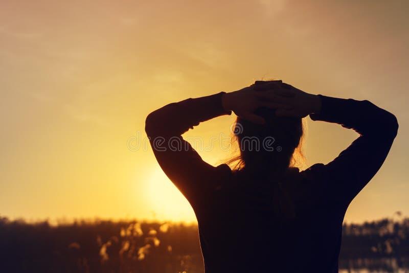Kontur av den unga kvinnan som ser solnedgången arkivbild
