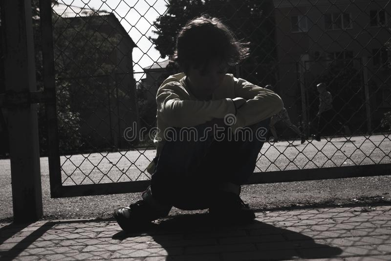 Kontur av den utomhus- lekplatsen för ledsen tonårig pojke K?nsligt deprimerat royaltyfria foton