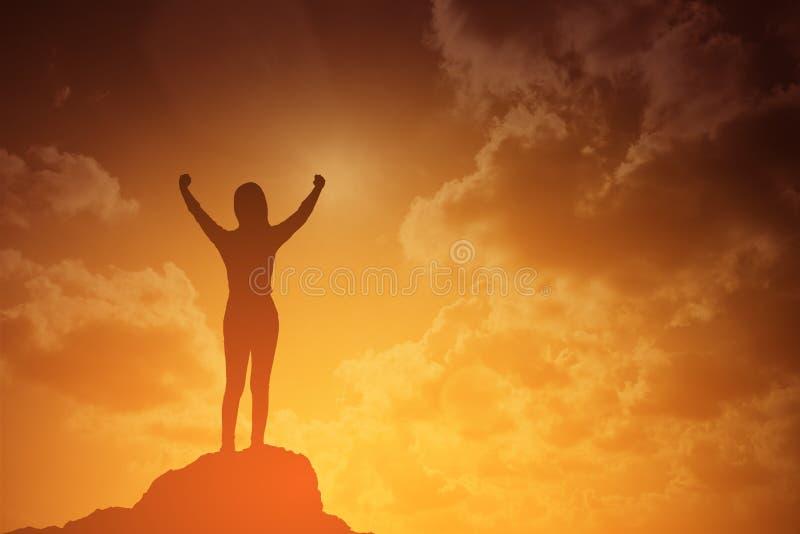 Kontur av den vinnande framgångkvinnan på solnedgången eller soluppgång som upp står och lyfter hennes hand i beröm affärsidé iso arkivbilder