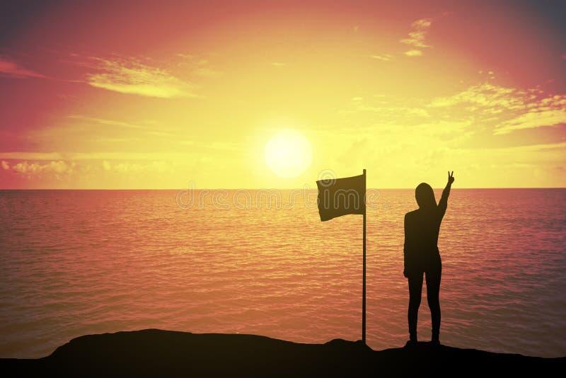 Kontur av den vinnande framgångkvinnan på solnedgången eller soluppgång som upp står och lyfter hennes hand nära flaggan i beröm royaltyfri foto