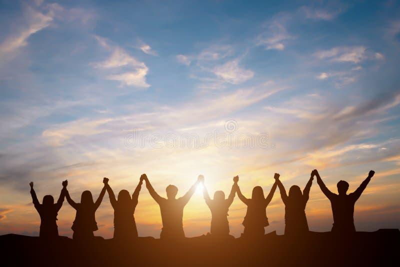 Kontur av det lyckliga affärslaget som gör höjdpunkthänder i solnedgången sk royaltyfri fotografi