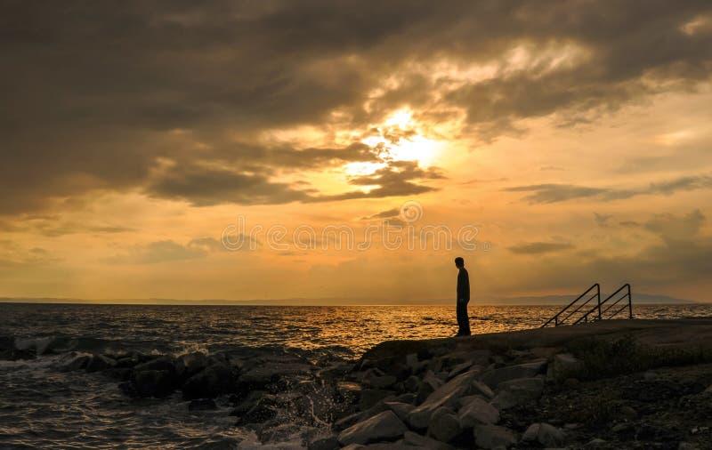 Kontur av det unga anseendet på stranden på solnedgången arkivfoto
