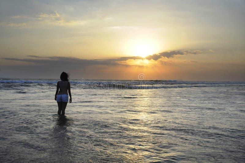 Kontur av det unga härliga asiatiska kvinnaanseendet på vatten som är fritt, och avkopplad seende solhorisont på solnedgångstrand arkivbild