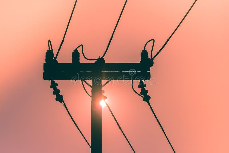 Kontur av elektricitetspolen och den höga spänningskraftledningen med solnedgång i bakgrunden royaltyfri fotografi