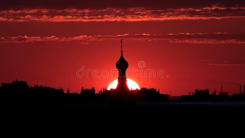Kontur av en överkant av en kyrka ett djupt - röd solnedgång royaltyfria bilder